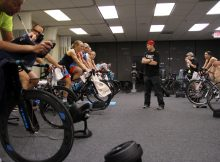 group of athletes training on stationary bicycles in a room
